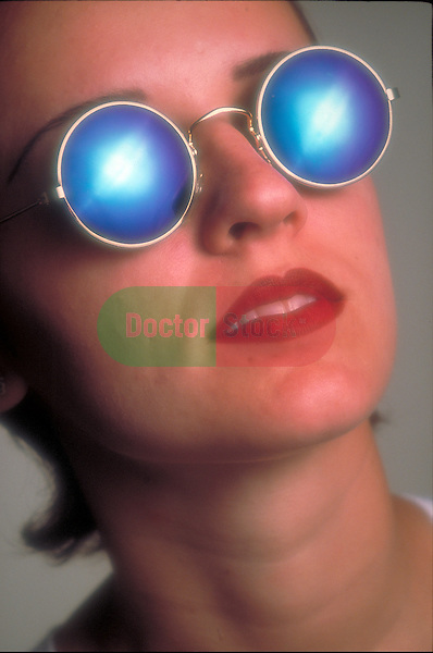young woman with sunglasses looking into bright light
