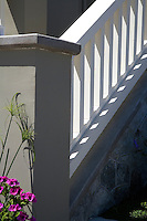 A fine art landscape image of a pattern of stairs with a grey, white and pale olive color scheme, accented with bright fuschia-colored flowers and green grasses, with the vertical and square patterns offset by rounded grey stone patterns. Shadows from bright sunlight add to the abstract design.