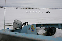 Ken Anderson on the Unalakleet slough shortly after leaving the checkpoint with a fishing boat in the foreground.   2005 Iditarod Trail Sled Dog Race.