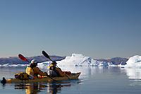 Sea kayakers paddling among icebergs on Sermilik Fjord near settlement of Tiniteqilaq, East Greenland
