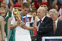FIFA President Sepp Blatter presents the World Cup trophy to Philipp Lahm of Germany