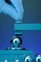 Ball Bearing Testing; measurement, equipment, gloved fingers applying machinery, blue background.