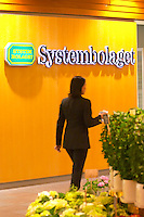 A neon sign saying Systembolaget, the Swedish retail monopoly stores for alcohol wine beer spirits and flowers in a flower shop in the foreground. A woman in black walking past Stockholm, Sweden, Sverige, Europe