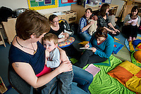 """A mother breastfeeding her toddler at a drop-in breastfeeding support centre.<br /> <br /> Image from the """"We Do It In Public"""" documentary photography project collection: <br />  www.breastfeedinginpublic.co.uk<br /> <br /> Dorset, England, UK<br /> 17/04/2013"""