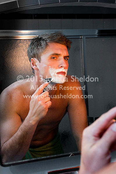Reflection of young man shaving in mirror