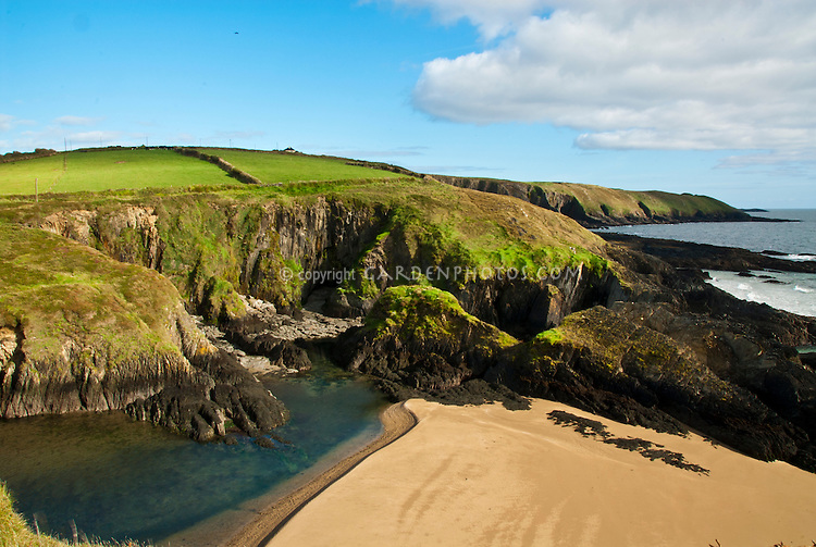 South Ireland Irish coast with sea, hidden swimming cove near Dunworley Beach, blue skies, clouds, sand, green fields, ocean, cove, County Cork, Celtic Sea