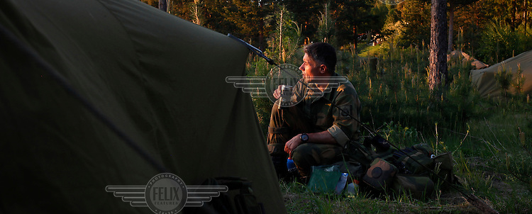 Alexander Brodahl Moxnes have a cup of coffee outside his tent as the sun sets. Norwegian Home Guard soldiers during exercise Djerv..The Home Guard has traditionally been designated to secure important  domestic installations in case of war or crisis. With the cold war long gone, a war in Afghanistan and budget cuts, there is a debate over the Home Guard's role in the future.