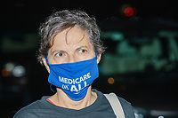 """A person wears a facemask reading """"Medicare for All"""" as people, including some party delegates, gather to watch the 2020 Democratic National Convention at a """"Ridin' with Biden"""" Drive-In Theater viewing event at Suffolk Downs in Boston, Massachusetts, on Wed., Aug. 19, 2020."""