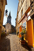 Narrow street with colourful shops looking towards the Bell tower of the Wooden Church of St Terezza - Market Square HonfleurNormandy France