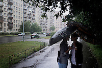 Sheltering from the rain beneath umbrellas, girlfriends meet after work. On 30 June 2013, Russian President Vladimir Putin signed into law an ambiguous bill banning the 'propaganda of nontraditional sexual relations to minors'. The law met with widespread condemnation from human rights and LGBT groups. (MANDATORY CREDIT   photo: Mads Nissen/Panos Pictures /Felix Features)
