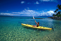 Girl paddles yellow kayak through clear water at Napili Bay, Maui.