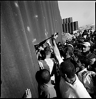 Rafah, Gaza strip, Sept 14 2005.Passing an toy air gun throught the wall. Palestinians find gaps in the the 8 meter high wall  separating the Palestinian city from Egypt. Thousands  rushed across the border in an incredible chaos to visit relatives for the first time in 18 years and ... to bring back cheap Egyptian goods such as cigarets or gazoline.