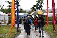 Sunday 25 May 2014, Hay on Wye, UK<br /> Pictured: People arriving at the festival ground holding an umbrella as the rain starts again.<br /> Re: The Hay Festival, Hay on Wye, Powys, Wales UK.