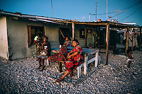 Women enjoy a fresh evening breeze outside their home.