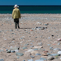 Woman in hat walking on beach, Isle of Man.
