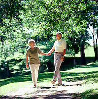 Older couple walking in par