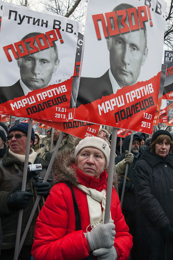 Moscow, Russia, 13/01/2013..Thousands of opposition protesters carry posters of President Vladimir Putin and members of the Russian parliament with the word ?Shame? written in red at a protest called the March Against The Scoundrels. The protest was against the new law banning the adoption of Russian children by Americans, widely seen as a response to the recently passed USA Magnitsky Act.