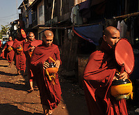 Monks walk through a village begging for a food in the centre of  Rangoon, Burma, NOV 2008.  Monks are given food by the population in this Buddhist country.<br />