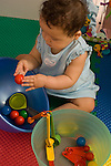 9 month old baby girl sitting holding small ball with finger tips