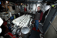 Captain David Janka shows off the diesel engine which propels the M/V Auklet in Prince William Sound, Southcnetral Alaska on a spring evening in early May.