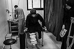 GAZA, Palestine: Oum Ahmed is doing some exercises with the help of an MSF physiotherapist who notices her improvements since the last session and measures the level of her pain to adapt her treatment and avoid addiction to pain killers, the 27th of October 2019. Three times a week, Oum Ahmed goes to the MSF (Médecins sans frontière) clinic where she receives proper treatment and medication.   <br /> <br /> GAZA, Palestine: Oum Ahmed fait quelques exercices avec l'aide d'un physiothérapeute de MSF qui a constaté des améliorations depuis la dernière session et mesure son niveau de douleur pour adapter son traitement et éviter la dépendance aux analgésiques, le 27 octobre 2019. Trois fois par semaine, Oum Ahmed se rend à la clinique MSF (Médecins sans frontière) où elle reçoit un traitement et des médicaments appropriés.