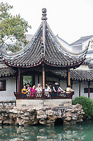 Suzhou, Jiangsu, China.  Tourists in Pavilion Overlooking Garden Pond, House of the Master of the Nets.