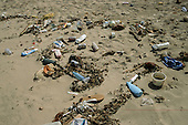 Itaparica Island, Bahia State, Brazil. Rubbish on the beach; plastic bottles, flip-flop sandals, beer cans, milk cartons, containers and seaweed.