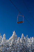 Empty chairs on a chairlift hang above trees at Showdown Ski Area on King's Hill in the Little Belt Mountains near Neihart, Montana, USA.