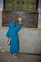 Fez, Morocco - Almsgiving.  A woman places a coin in the alms box at the Zawiya of Moulay Idris II, in Old Fez.