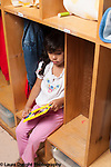 Education preschool 3-4 year olds separation sad girl sitting in cubby holding picture frame with mother's photo inside it vertical