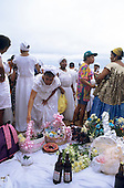 Salvador, Bahia, Brazil. Offerings spread out on a white sheet; Candomble religious festival of Iemanja.