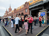 Couples tango dancing at the Oberbaumbrucke with a U-bahn train passing overhead. The bridge is a Berlin landmark connecting the districts of Friedrichshain and Kreuzberg across the River Spree, districts that were divided by the Berlin Wall. During the Cold War the bridge was a border post and exchange point for spys. It has now become a symbol of a united Berlin and is the location for a Sunday market..
