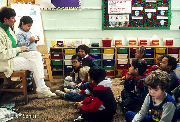 MR / Schenectady, New York. Yates Arts-in Education Magnet School / Inclusion group with mainstreamed special education students. Teacher leads daily meeting with first grade and special education students. Boy standing (Down syndrome, Peruvian-American) holds word cards about weather. Boy in right foreground (age 8, autism) has difficulty paying attention. Group includes students with various disabilities including autism, ADHD, Down syndorme, and developmental disabilities. MR: SNB © Ellen B. Senisi