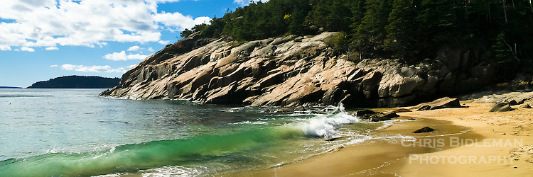 Moment before wave break on beach in Arcadia National Park, Maine.  White clouds are seen in the blue sky above the trees in this panoramic rendering.