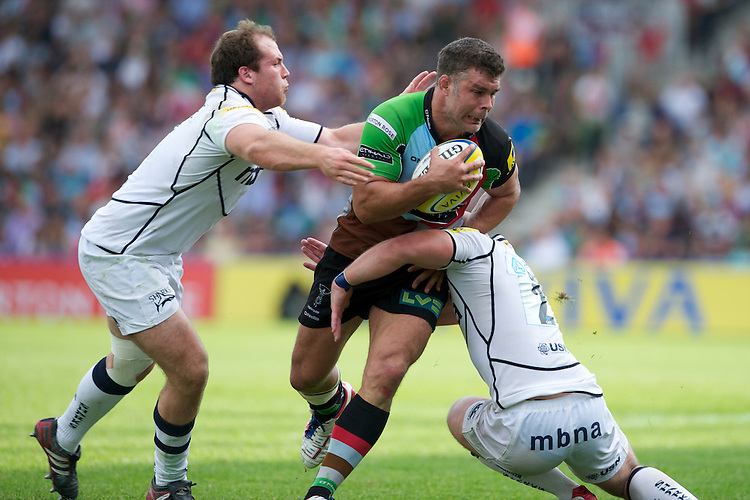 Nick Easter of Harlequins is tackled by Henry Thomas and Joe Ward of Sale Sharks during the Aviva Premiership match between Harlequins and Sale Sharks at The Twickenham Stoop on Saturday 15th September 2012 (Photo by Rob Munro)
