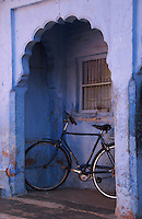 """A bicycle parked in the arched verandah of a traditional house makes an interesting focal point in the """"Blue City"""" of Jodhpur, Rajasthan, India."""