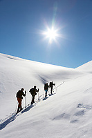 A group of four ski up a snowy slope on a sunny day in the Brooks Range mountains, Arctic, Alaska.