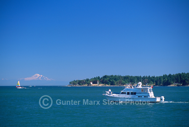 Boats leaving Active Pass in the Southern Gulf Islands, at Mayne Island, British Columbia, Canada, with Mt. Baker, in Washington State, USA, on the Horizon