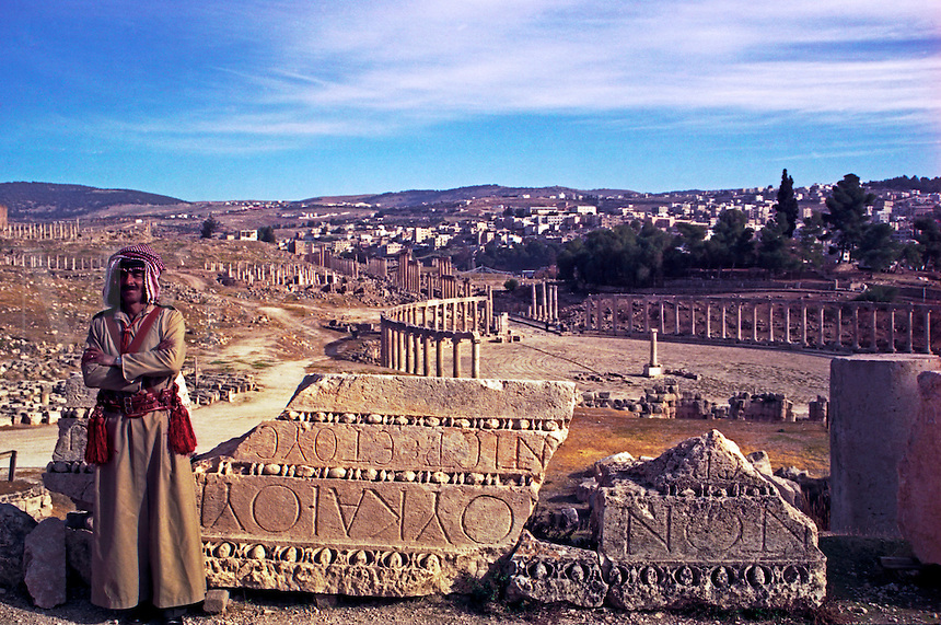 Jordan, The Middle East. Policeman on duty at Jerash ( Ancient Gerasa ) with the Oval Forum in the background..Model Released