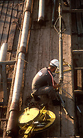 Oil rig worker rigging wireline tools