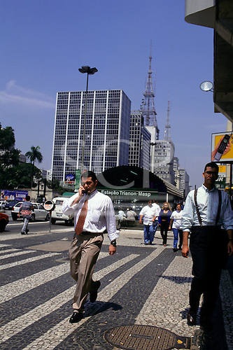 Sao Paulo, Brazil. Businessmen in shirts, one talking on a mobile phone, outside Trianon metro station.