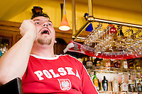 Poland fan Andy watches his team's World Cup match against Germany on June 14, 2006 at the Fireplace, a bar in a Polish section of Brooklyn.<br /> <br /> The World Cup, held every four years in different locales, is the world's pre-eminent sports tournament in the world's most popular sport, soccer (or football, as most of the world calls it).  Qualification for the World Cup is open to any country with a national team accredited by FIFA, world soccer's governing body. The first World Cup, organized by FIFA in response to the popularity of the first Olympic Games' soccer tournaments, was held in 1930 in Uruguay and was participated in by 13 nations.    <br /> <br /> As of 2010 there are 208 such teams.  The final field of the World Cup is narrowed down to 32 national teams in the three years preceding the tournament, with each region of the world allotted a specific number of spots.  <br /> <br /> The World Cup is the most widely regularly watched event in the world, with soccer teams being a source of national pride.  In most nations, the whole country is at a standstill when their team is playing in the tournament, everyone's eyes glued to their televisions or their ears to the radio, to see if their team will prevail.  While the United States in general is a conspicuous exception to the grip of World Cup fever there is one city that is a rather large exception to that rule.  In New York City, the most diverse city in a nation of immigrants, the melting pot that is America is on full display as fans of all nations gather in all possible venues to watch their teams and celebrate where they have come from.