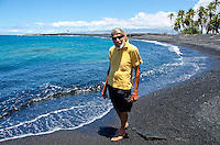 A local man walks the shore of Keawaiki Bay's mostly black sand beach, Big Island; this area also had an ancient Hawaiian settlement and temple (or heiau) and was affected by the 1859 Mauna Loa eruption.