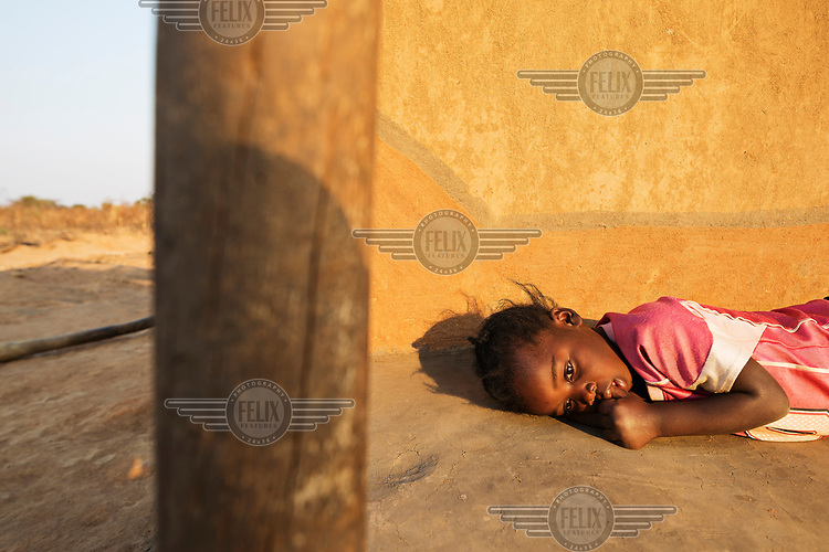 Catherine (3), feeling unwell, lies on the ground outside her home.