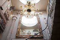 A vast gilt-framed mirror dominates the stairwell at Aynhoe Park