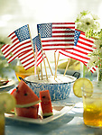 An outdoor table for a 4th of July celebration. Centerpiece with small American flags, glasses of iced tea, flowers, and watermelon slices