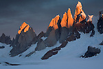 Sunlight only reaches the very tips of the peaks of the granite facade of the southern Andes.