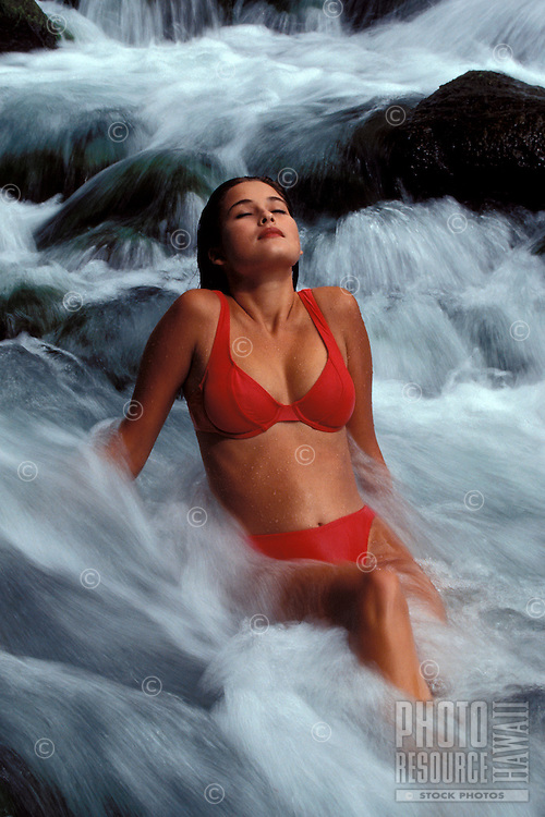A woman relaxes in a waterfall at Iao Valley, Maui.