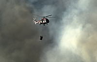 Pictured: A fire helicopter en route to douse the flames.<br /> Re: A forest fire has been raging in the area of Kalamos, 20 miles east of Athens in Greece. There have been power cuts, country houses burned and children camps evacuated from the area.