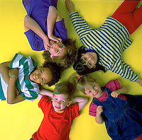 Portrait of 5 children aged 5 to 10 years old, lying on their backs, facing the camera, heads together, all with different expressions forming a graphic shape. 5 children. United States.